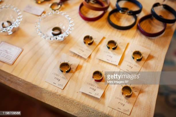 high angle close up of finger rings and leather bracelets on a table in a leather shop. - jewellery stock pictures, royalty-free photos & images