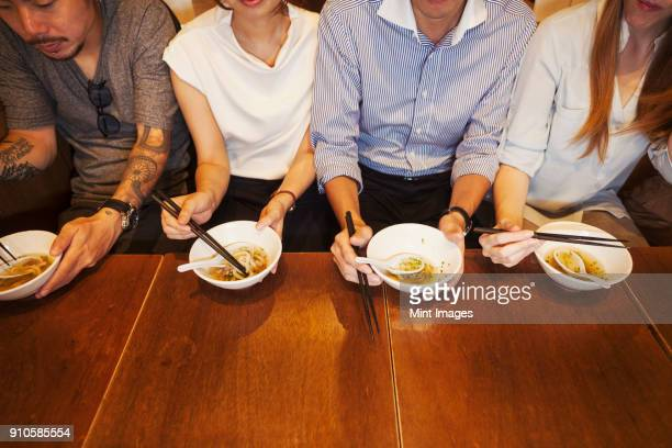 High angle close up of four people sitting side by side at a table in a restaurant, eating from bowls using chopsticks.