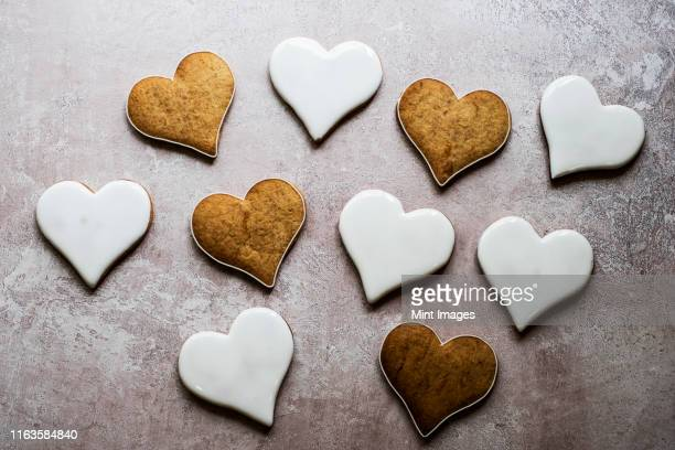 high angle close up of freshly baked hart-shaped cookies decorated with white icing. - icing stock pictures, royalty-free photos & images