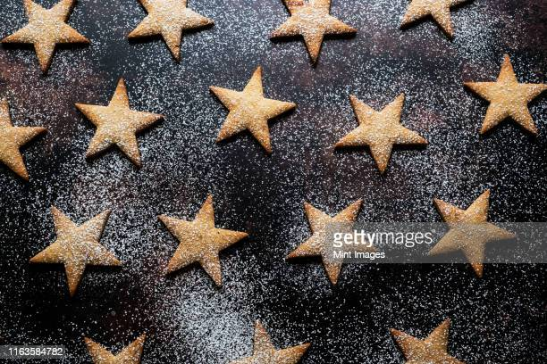 high angle close up of freshly baked star-shaped cookies dusted with icing sugar on black background. - icing sugar stock pictures, royalty-free photos & images