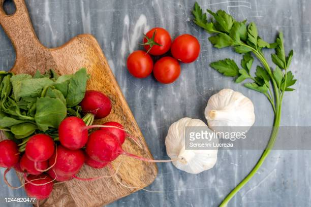 high angle close up of freshly picked radishes, garlic and flat leaf parsley and wooden chopping board on grey marble. - flat leaf parsley stock pictures, royalty-free photos & images