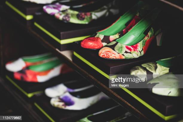 high angle close up of heeled shoes with colourful floral patterns on brown boxes lined up on wooden shelves. - シューズボックス ストックフォトと画像