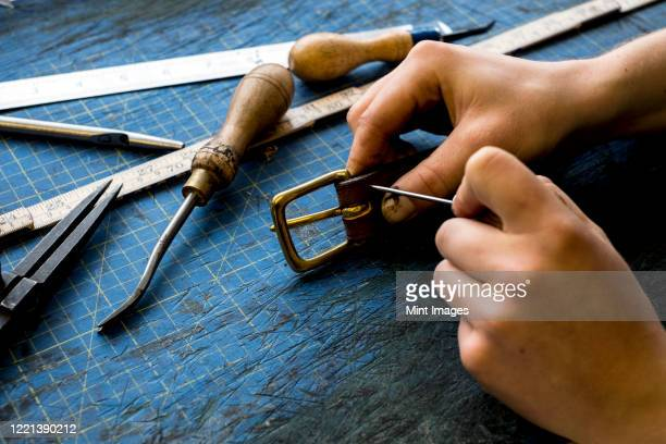 high angle close up of person working in saddler's workshop, attaching buckle to leather strap. - strap stock pictures, royalty-free photos & images