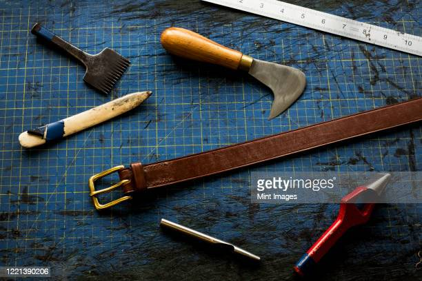 high angle close up of selection of saddle making hand tools. - strap stock pictures, royalty-free photos & images