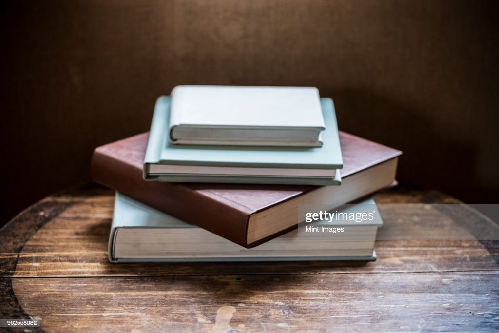 High angle close up of stack of book s on wooden table. : Foto de stock