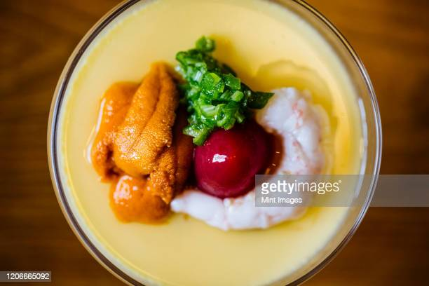high angle close up of uni chawanmushi, a chilled egg custard. - chawanmushi stock pictures, royalty-free photos & images