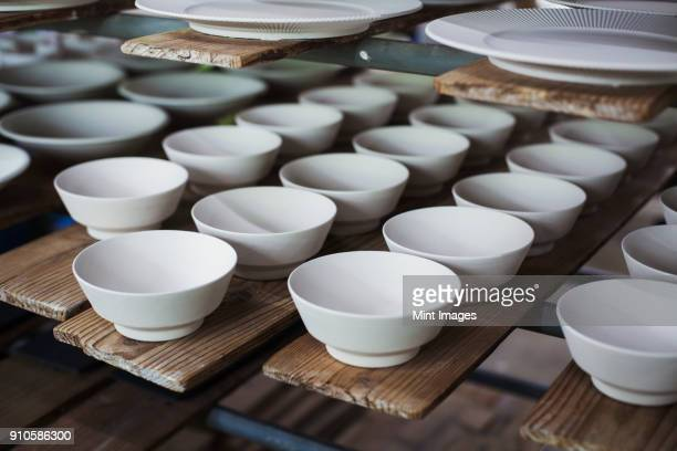 high angle close up of white bowls and plates in a japanese porcelain workshop. - ceramic stock photos and pictures