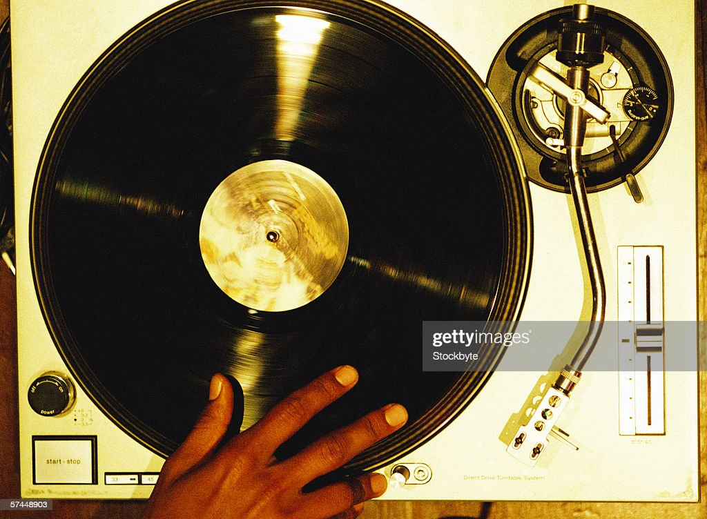 high angle close-up of a hand scratching a vinyl record on a turntable : Stock Photo