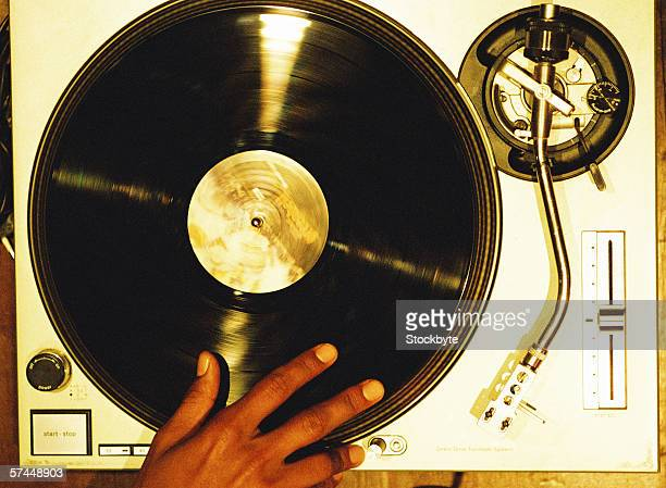 high angle close-up of a hand scratching a vinyl record on a turntable - クラブdj ストックフォトと画像