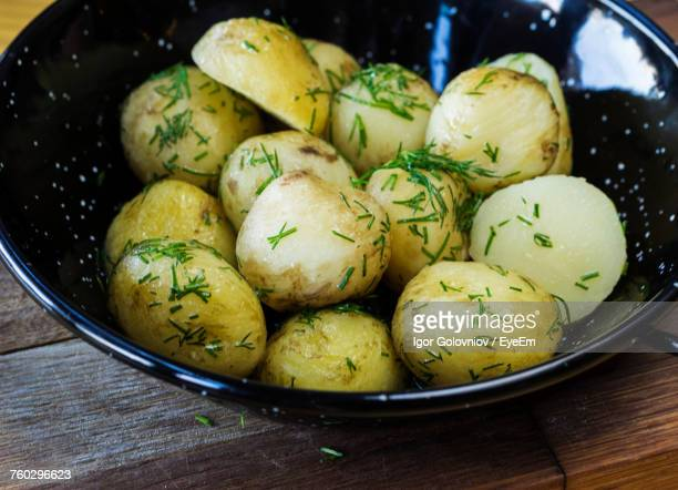 high angle close-up of boiled potatoes with dill served in bowl on wooden table - igor golovniov stock pictures, royalty-free photos & images