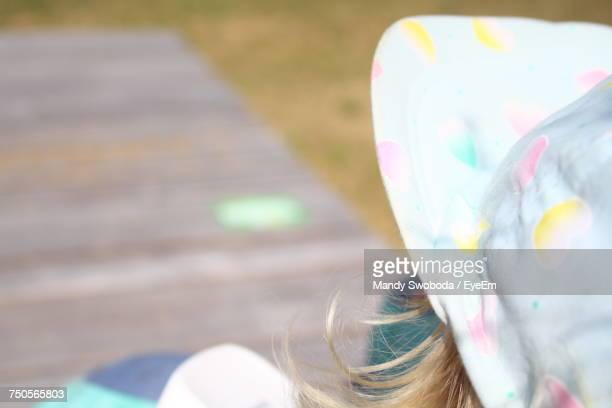 High Angle Close-Up Of Girl In Hat Sitting At Yard During Sunny Day