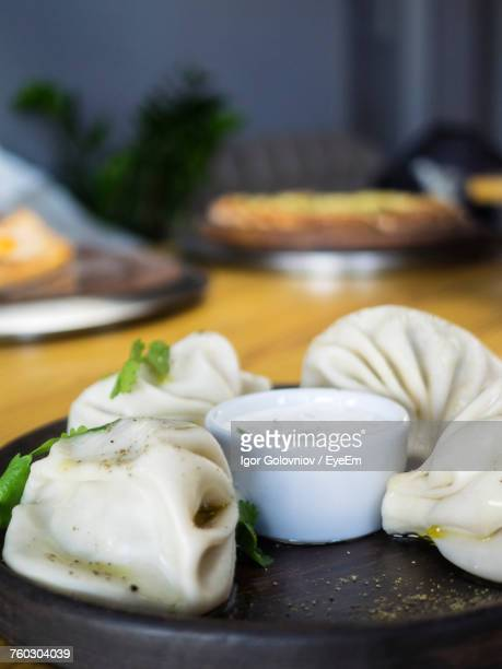 high angle close-up of khinkali with dip served in plate on wooden table - igor golovniov stock pictures, royalty-free photos & images