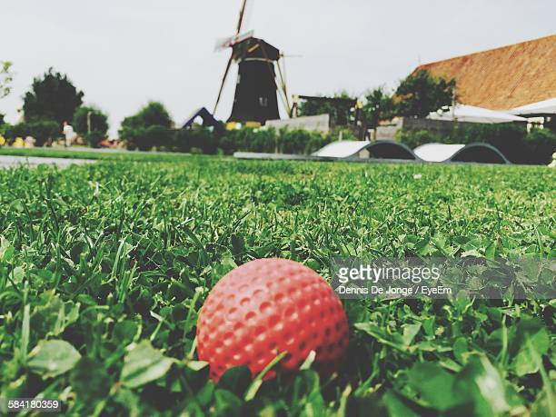High Angle Close-Up Of Red Golf Ball On Grass Against Windmill