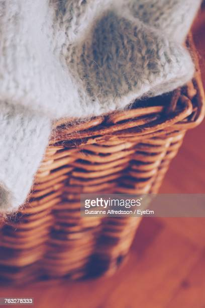 High Angle Close-Up Of Wicker Basket With Sweater On Floor