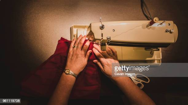 High angle cropped hands of woman using sewing machine at workshop