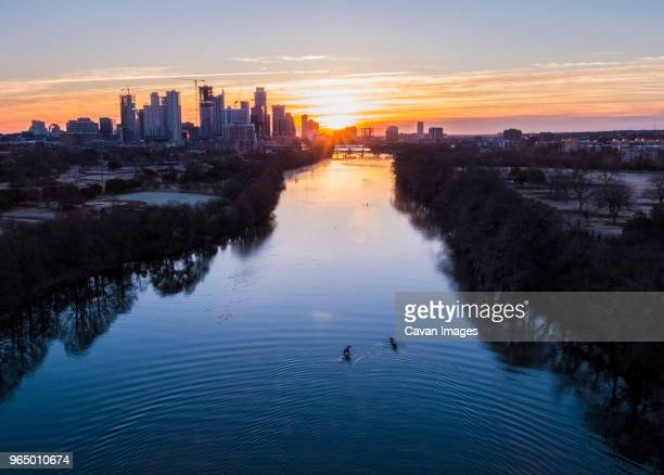High angle distant view of people sculling on Lady Bird Lake against cityscape during sunrise
