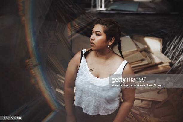 high angle fish-eye lens shot of overweight woman looking away outdoors - fat asian woman stock pictures, royalty-free photos & images