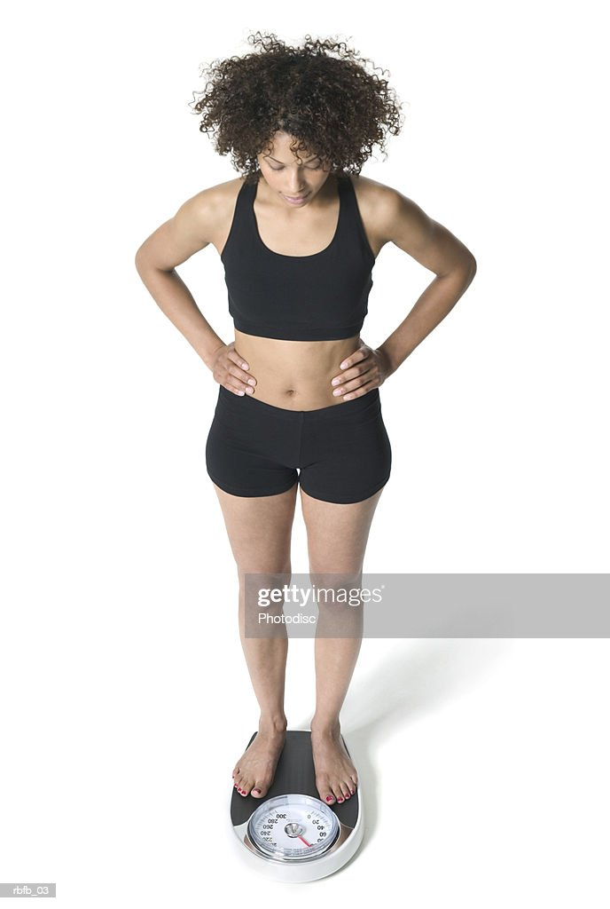 high angle full body of a young adult woman in a black workout outfit as she stands on the scale : Stockfoto