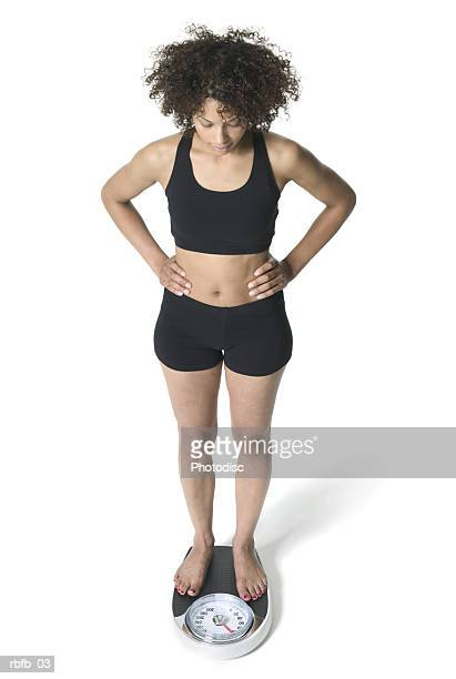 high angle full body of a young adult woman in a black workout outfit as she stands on the scale