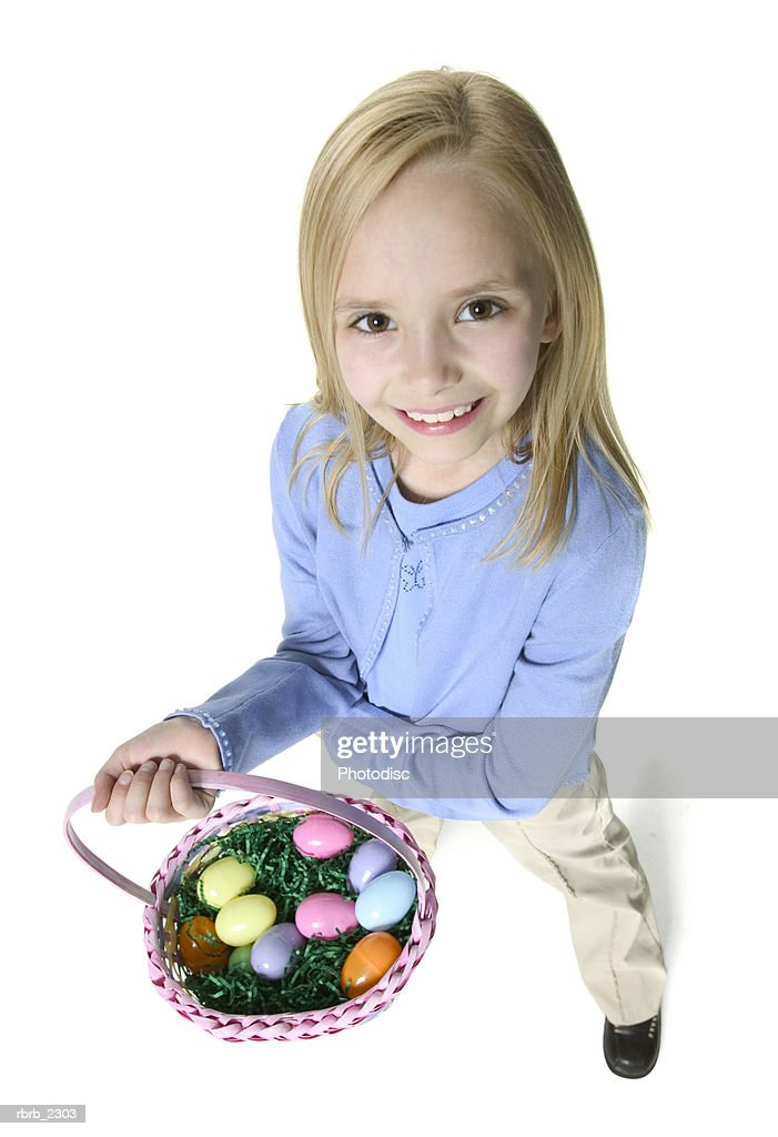 high angle full body shot of a blonde female child as she holds up an easter basket : Foto de stock