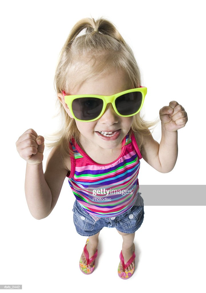 high angle full length shot of a female child in sunglasses as she looks up at the camera : Foto de stock