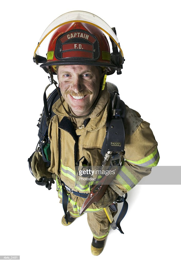 high angle full length shot of an adult male fireman as he smiles up at the camera : Foto de stock
