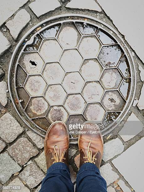 High Angle Low Section Of Man Standing On Manhole