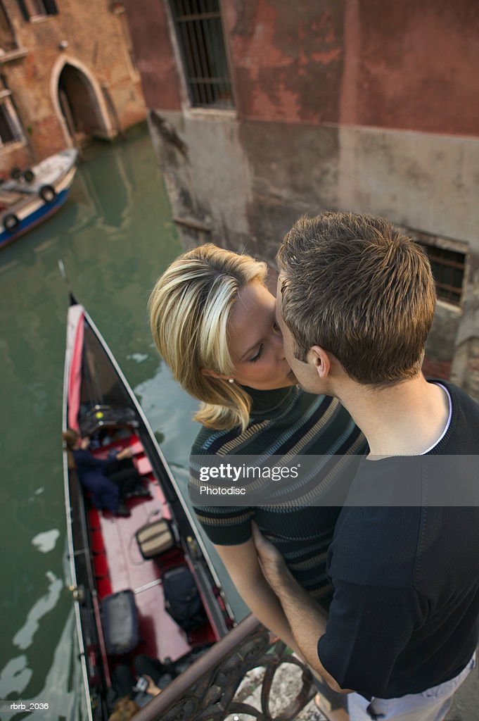 high angle medium shot of a young adult couple as they hug and kiss while in venice : Stock Photo
