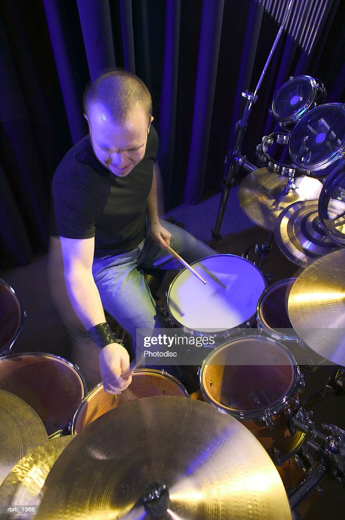 high angle medium shot of a young adult male as he plays his drums up on stage : Stockfoto