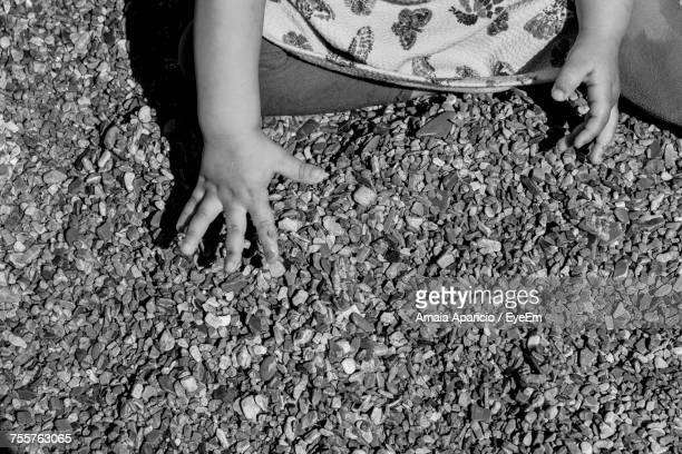 High Angle Midsection Of Girl Playing With Pebbles At Beach During Sunny Day
