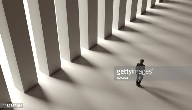 high angle of a senior businessman walking - column stock pictures, royalty-free photos & images