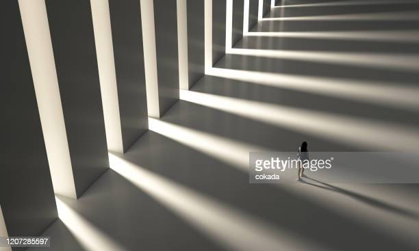 high angle of a young woman walking on corridor - column stock pictures, royalty-free photos & images