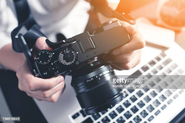 high angle of person with camera and laptop - digital camera stock pictures, royalty-free photos & images