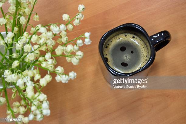 high angle of spring flowers lily of the valley and coffee cup on wooden table - bouquet de muguet fotografías e imágenes de stock