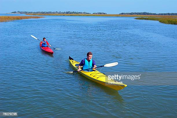 high angle of two boys kayaking along a marsh creek. - sumpmark bildbanksfoton och bilder