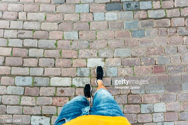 high angle personal perspective view of man in shorts and sneakers walking on a cobbled street - 探検家 ストックフォトと画像