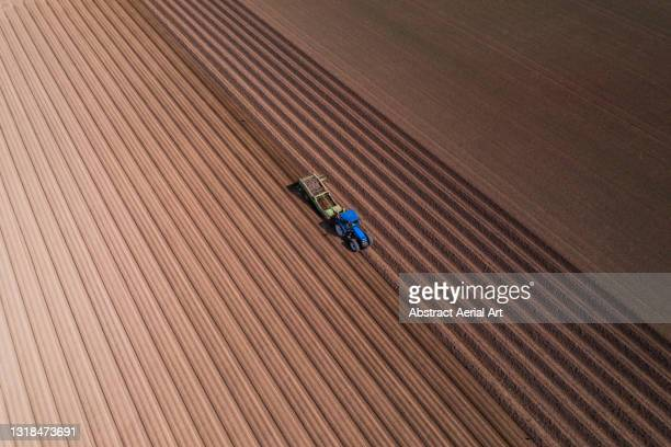 high angle perspective showing a tractor working in a plowed field, england, united kingdom - crop stock pictures, royalty-free photos & images