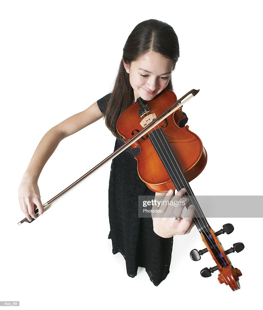 high angle portrait of an asian teenage girl in a black dress as she plays her violin : Foto de stock