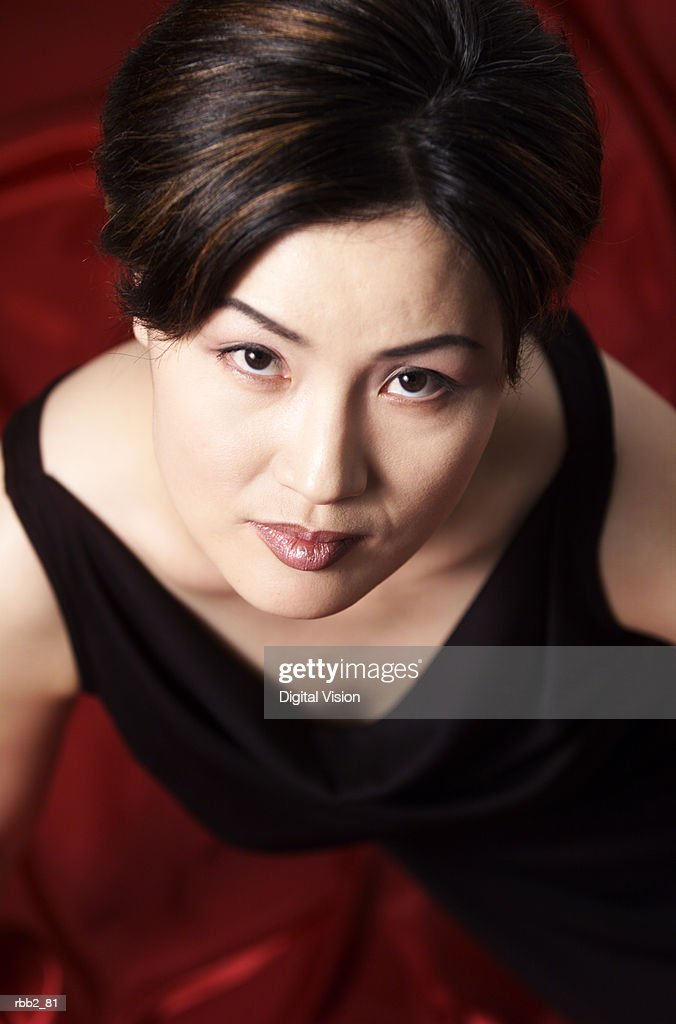 high angle portrait of an attractive asian female in a black dress  as she solemnly looks up into the camera : Stockfoto