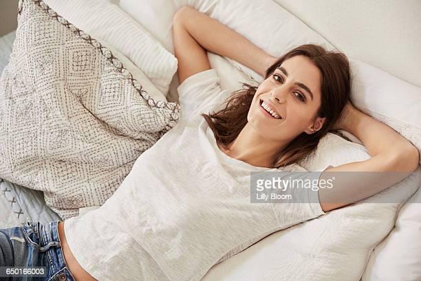 high angle portrait of beautiful young woman lying on bed - hände hinter dem kopf stock-fotos und bilder