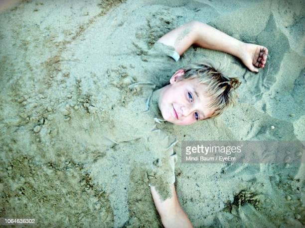 high angle portrait of boy buried in sand at beach - baum stock pictures, royalty-free photos & images