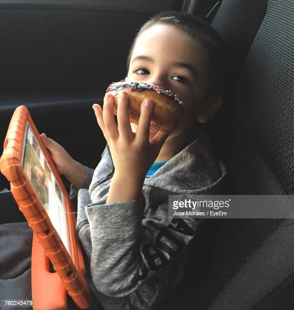 High Angle Portrait Of Boy Eating Donut While Sitting In Car