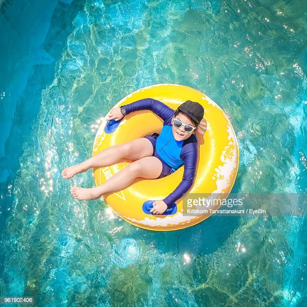 High Angle Portrait Of Boy In Inflatable Ring On Swimming Pool