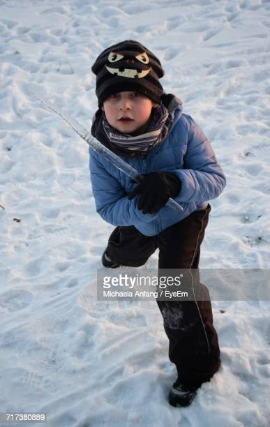 high angle portrait of boy playing with icicle on snow - anfang stock pictures, royalty-free photos & images