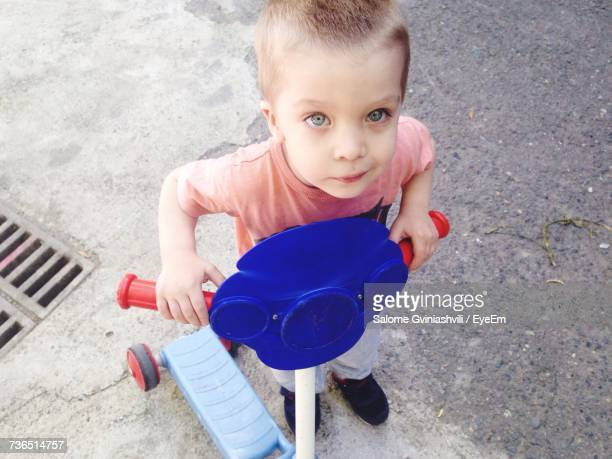 High Angle Portrait Of Boy Riding Push Scooter On Footpath