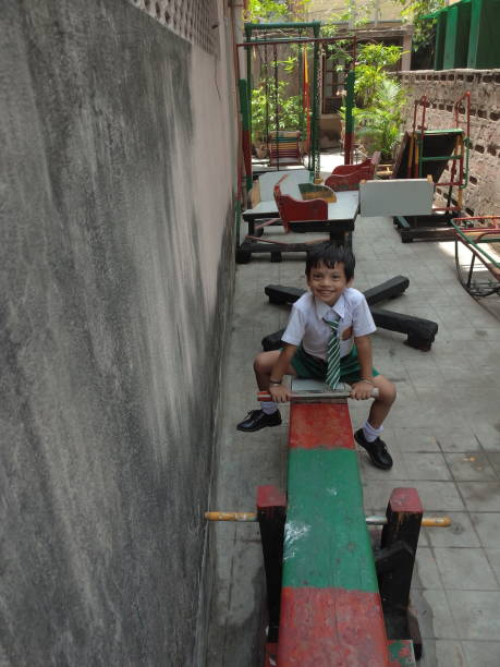 High Angle Portrait Of Boy Sitting On Equipment In Playground