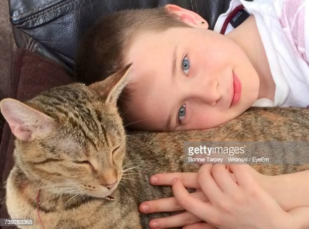 High Angle Portrait Of Boy With Cat Resting On Chair
