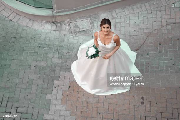 High Angle Portrait Of Bride In Wedding Dress Standing On Footpath