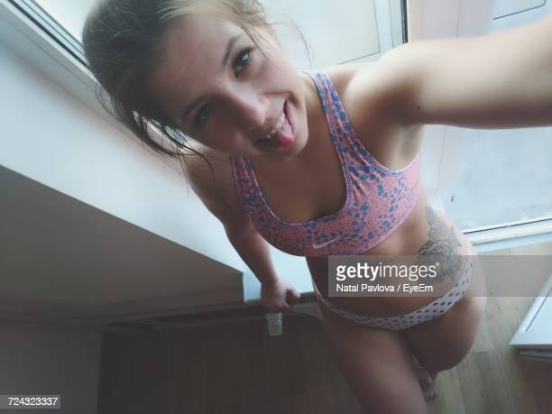 High Angle Portrait Of Cheerful Woman Wearing Lingerie Standing Against Glass Door At Home