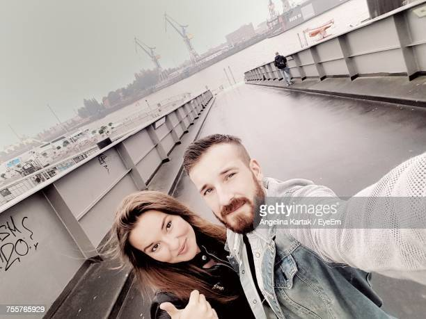 High Angle Portrait Of Couple Standing On Bridge By Sea